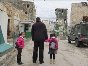 Ein zögernder Vater vor einem der Checkpoints mit seinen beiden Töchtern auf dem Schulweg