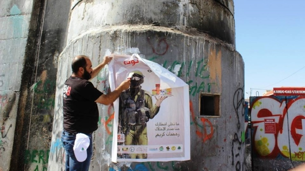 A campaigner in the West Bank puts up a poster in support of a campaign during Ramadan encouraging people to boycott Israeli products. Community boycott campaigns are spreading across the West Bank and the whole of Palestine.